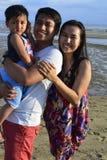 获得的家庭摆在为在白色沙子海滩的图片的乐趣在低潮 免版税库存图片