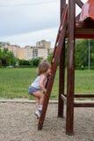获得的小女孩在操场的乐趣 免版税库存照片