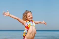获得的小女孩在海滩的乐趣 库存图片