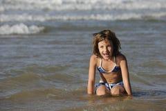 获得的小女孩在海滩的乐趣 库存照片