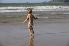 获得的小女孩在海滩的乐趣 免版税库存图片