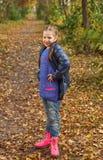 获得的小女孩美好的秋天的乐趣 免版税图库摄影