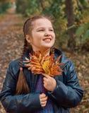 获得的小女孩美好的秋天的乐趣 图库摄影