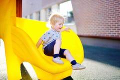 获得的小男孩在幻灯片的乐趣在操场 免版税图库摄影