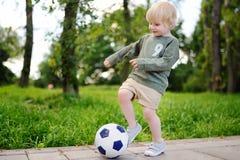 获得的小男孩打足球赛的乐趣在晴朗的夏日 免版税库存图片