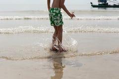 获得的小男孩跳跃在海滩的乐趣在天时间 库存照片
