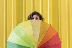 获得的少妇与一把五颜六色的伞的乐趣在黄色后面 免版税库存图片