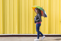 获得的少妇与一把五颜六色的伞的乐趣在黄色后面 免版税图库摄影