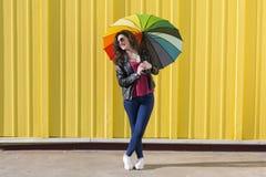 获得的少妇与一把五颜六色的伞的乐趣在黄色后面 免版税库存照片