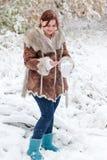 获得的少妇与雪的乐趣在冬日 免版税图库摄影