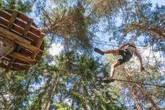 获得的少年在高绳索的乐趣在一个森林里追猎,冒险公园,爬树在夏天 库存照片