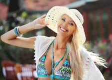 获得的帽子的相当微笑的白肤金发的妇女室外的乐趣 库存图片