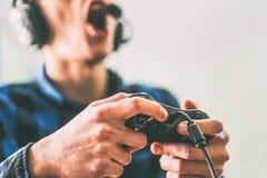 获得的年轻人在网上打电子游戏的乐趣使用耳机和话筒-拿着控制杆的男性手游戏玩家的关闭 免版税图库摄影