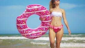 获得的年轻女人乐趣用在海滩的玩具可膨胀的圆环多福饼 影视素材