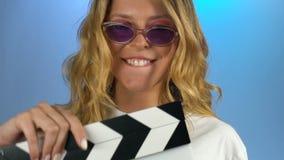 获得的年轻女人使用以clapperboard、驱动和放肆的乐趣 股票视频