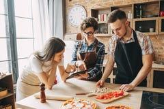 获得的朋友一起烹调食物的乐趣在厨房 烹饪, t 图库摄影