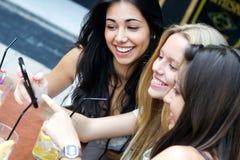 获得的朋友与智能手机的乐趣 免版税库存照片