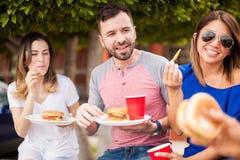 获得的朋友吃汉堡和乐趣 免版税库存图片