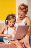 获得的母亲和的女儿与笔记本的乐趣 免版税库存照片