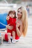 获得的母亲和的女儿乐趣外面在船坞 图库摄影
