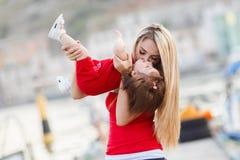 获得的母亲和的女儿乐趣外面在船坞 免版税库存照片