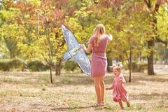 获得的母亲和的女儿在公园背景的乐趣 飞行风筝的家庭 母性概念 复制空间 库存照片