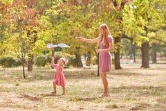 获得的母亲和的女儿在公园背景的乐趣 飞行风筝的家庭 母性概念 复制空间 免版税库存照片