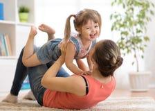 获得的母亲和的女儿在地板上的一个乐趣在家 一起放松的妇女和的孩子 免版税库存图片