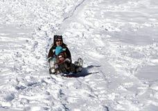 获得的母亲和的子项在雪撬小山的乐趣 库存照片