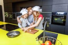 获得的母亲和的孩子烹调在厨房里和乐趣 免版税库存图片