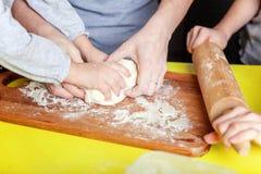获得的母亲和的孩子烹调在厨房里和乐趣 免版税图库摄影