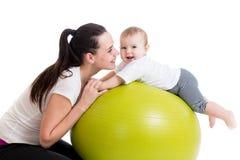 获得的母亲和的婴孩与体操球的乐趣 免版税库存图片
