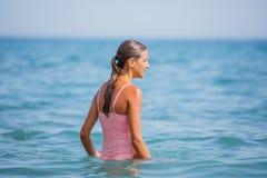 获得的泳装的女孩在热带海滩的乐趣 库存图片