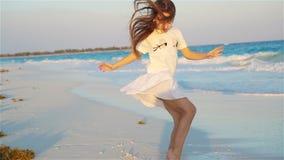 获得的海滩的活跃小女孩很多乐趣 在海滨的运动的孩子跳舞 影视素材