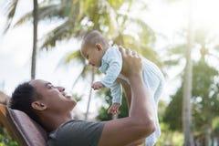 获得的父亲与他的婴孩的乐趣 免版税库存照片