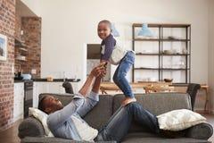 获得的父亲和的儿子一起使用在沙发的乐趣 免版税库存照片