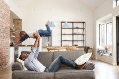 获得的父亲和的儿子一起使用在沙发的乐趣 库存图片
