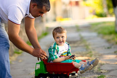获得的父亲和的儿子与玩具汽车的乐趣 免版税图库摄影
