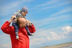 获得的父亲和的儿子在热带海滩的乐趣 免版税库存图片