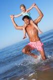 获得的父亲和的女儿在海滩的乐趣 图库摄影