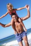 获得的父亲和的女儿在海滩的乐趣 免版税库存图片
