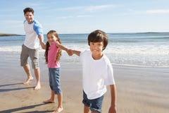 获得的父亲和的孩子海滩假日的乐趣 图库摄影