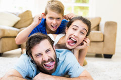获得的父母和的儿子画象说谎在地毯和乐趣 免版税库存照片