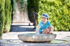 获得的男孩与喷泉射击的乐趣 库存照片