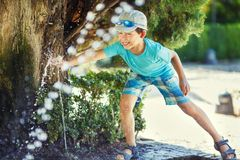 获得的男孩与喷泉射击的乐趣 免版税库存图片
