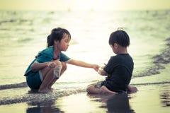 获得的男孩和的女孩在夏天海滩的乐趣与阳光 库存图片