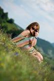 获得的礼服的美丽的妇女坐草和乐趣 图库摄影