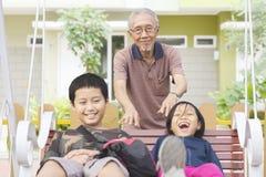 获得的祖父与他的孙的乐趣 免版税库存图片