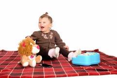 获得的婴孩与她的玩具的乐趣 免版税图库摄影