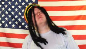 获得的Rastaman与他的dreadlocks的乐趣在美国旗子的背景 股票视频